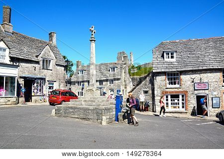CORFE, UNITED KINGDOM - JULY 19, 2016 - Stone cross in the village centre with the castle to the rear Corfe Dorset England UK Western Europe, July 19, 2016.