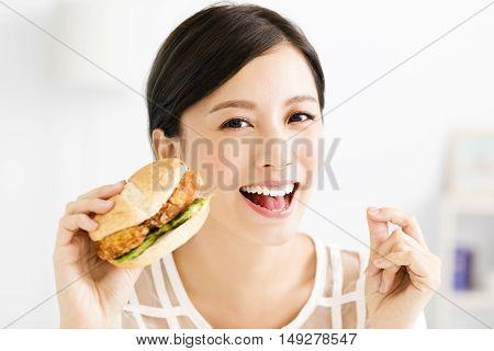 happy young asian woman eating big hamburger