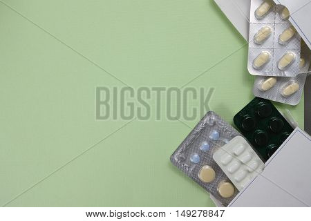 Different medical drugs illness relief concept copy space on light green background
