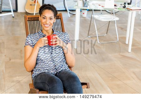 Portrait of smiling afro-american office worker sitting in offfice with mug