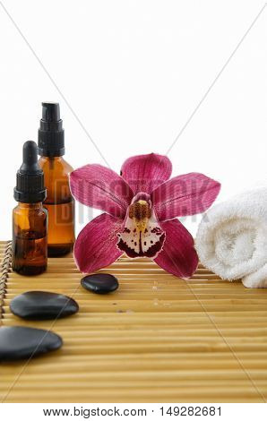 Spa setting with red orchid ,towel, oil ,stones with mat texture