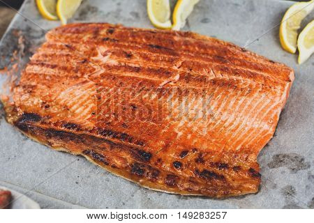 Salmon red fish juicy roasted fillet grilled on barbecue. Healthy seafood bbq outdoors at picnic, party.