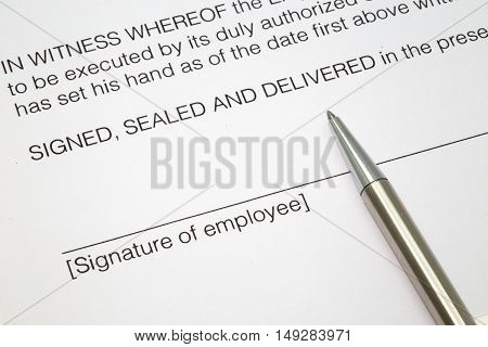 Close up of an employment contract with a line and the words signature of employee and a silver pen