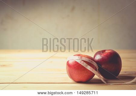 apples with measuring tape on wooden background vintage tone