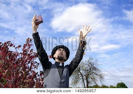 Young bearded priest with hands lifted to sky