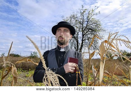 Young bearded priest on autumn tree background