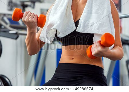 Close up middle part of woman hands and belly holding dumbbells at gym.