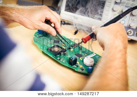 Tech tests electronic equipment in service center