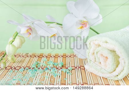 Spa concept: bath towels and bath salt on a natural mat and a branch of white orchid on a green background