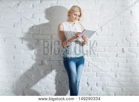 Young woman standing front of white brick wall, using tablet computer.