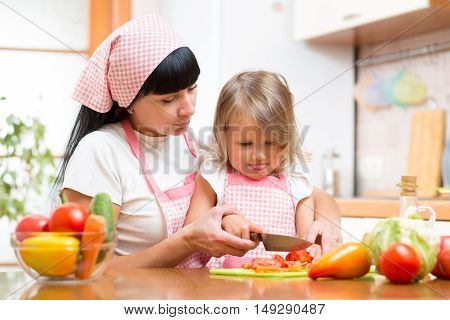 Mother Teaching Child Making Salad In Kitchen. Mom And Kid Chopping Vegetable On Cutting Board With