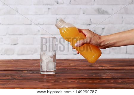 Woman try to pouring juice in glass with ice cubes