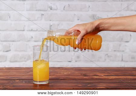 Woman's hand with bottle of juice pouring it in glass with ice cubes