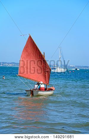 STUDLAND BAY, UNITED KINGDOM - JULY 19, 2016 - People sailing in a dinghy near the beach Studland Bay Dorset England UK Western Europe, July 19, 2016.