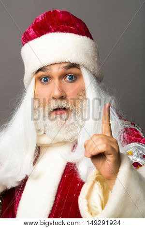 Amazed santa claus man in red Christmas suit got idea and makes hand gesture