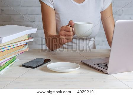 Girl holding white cup of coffee and thinks about the task