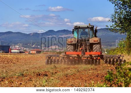 Red tractor ploughing field in autumn days