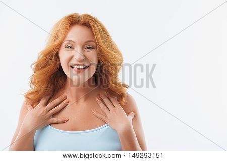 Joyful senior woman is expressing her happiness and smiling. She standing and gesturing. Isolated and copy space in right side