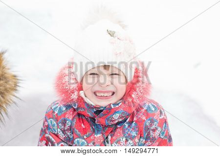Closeup Portrait Of Gerl In Winter Clothes Outside Playing In The Snow Drifts In The Winter - Russia