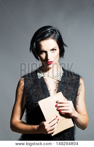 young sexy woman or girl with short brunette stylish hair and red lips on pretty face in black cloth holds paper envelope on grey background closeup