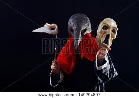 girl in a black cloak and a theatrical mask holding a scary masks