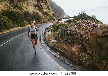 Fit female training outdoor in beautiful landscape. Young woman running on open highway on a rainy day.