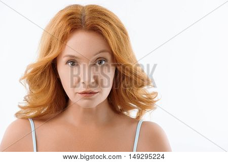 Senior woman is looking at camera with amazement. She is standing and raising her eyebrow up. Isolated and copy space in right side