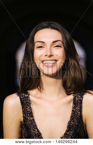young sexy sensual woman or girl portrait with long brunette hair and pretty smiling happy face in black vest sunny day outdoor in street
