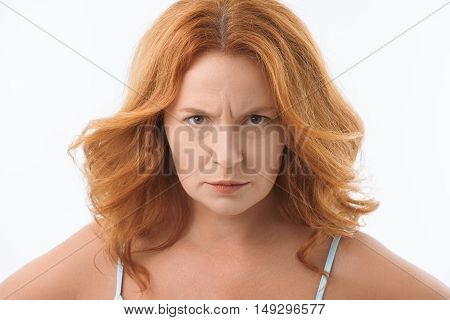 Angry middle-aged woman is looking at camera with annoyance. She is standing and posing. Isolated