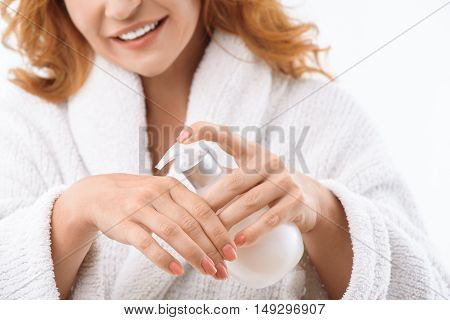 Cheerful middle-aged woman is squeezing cream on her hand. She is standing in bathrobe and laughing. Isolated