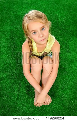 Funny little girl sitting on the grass, tucking her knees, and looking at the camera. Summer holidays.