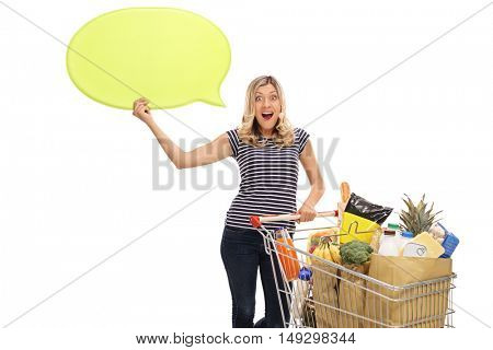 Cheerful woman posing with a shopping cart and a speech bubble isolated on white background