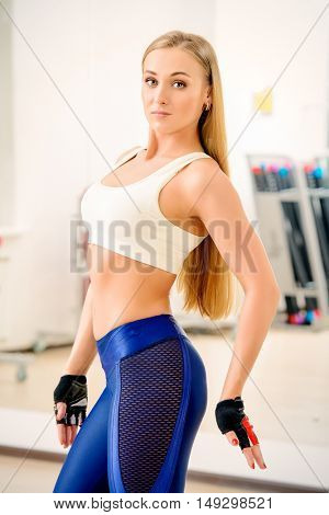 Beautiful athletic young woman working out in a gym. Healthy lifestyle. Sports, fitness, bodybuilding.