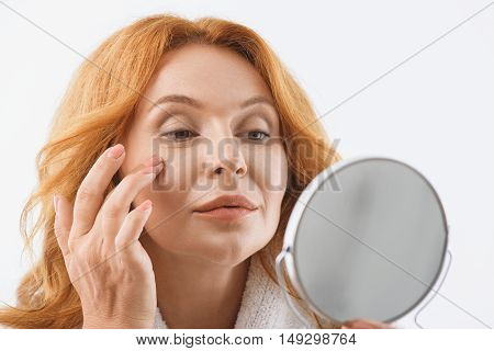 Confident middle-aged woman is touching her skin and looking at mirror with satisfaction. She is standing in white bathrobe. Isolated