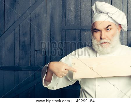 Bearded man cook with serious face holding and showing on empty wooden plate in chef uniform