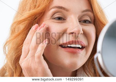 Close up of female face. Middle-aged woman is applying cream on her facial skin. She is looking at mirror and smiling