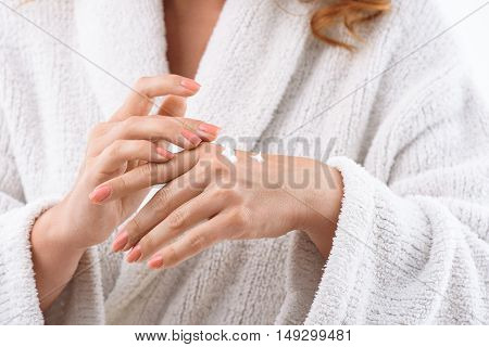 Close up of female arms applying cream on hand. Woman is standing in white bathrobe