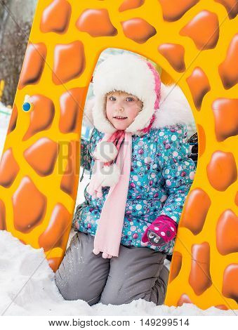 closeup portrait of happy laughing children in winter clothes outside playing in the snow drifts on the bright colorful playground in the winter - Russia Moscow - February 25 2016