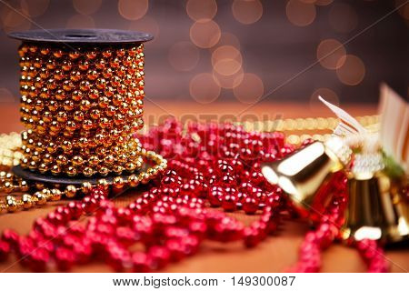 Christmas decoration. Chain red and golden ornamental beads on a reel and bells. Selective focus on the reel.