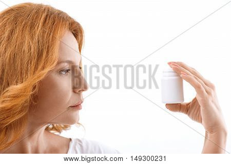 Ill middle-aged woman is holding jar of pills and looking at it with seriousness. Isolated