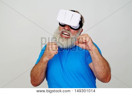 Man with white beard in VR-headset is standing in fighting pose with clenched fists isolated against white background