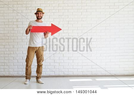 Happy stylish man is standing and holding big red arrow, white brick wall in background
