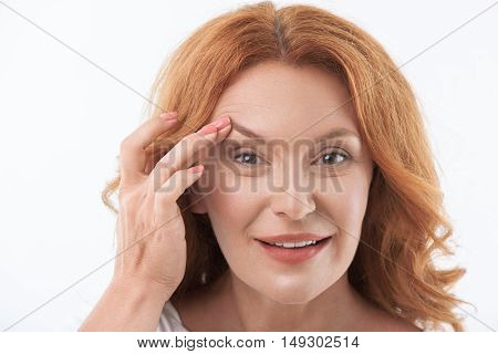 Happy senior woman is stretching her elastic skin under eye with satisfaction. She is looking forward and smiling. Isolated