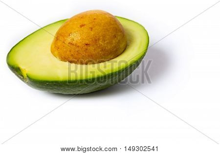 Cut in half open ripe avocado fruit with the pit isolated over the white background