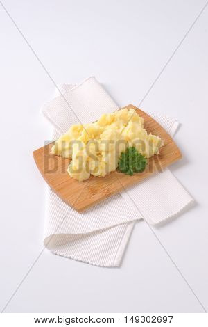 pile of mashed potatoes on wooden cutting board