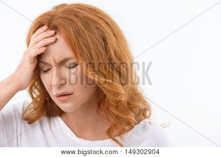 Frustrated senior woman feels pain in her head. She is standing and touching forehead. Her eyes are closed with despair. Isolated and copy space in right side