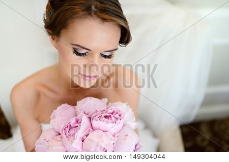 Beauty bride in bridal gown with bouquet and lace veil indoors. Beautiful model girl in a white wedding dress. Female portrait of cute lady. Woman with hairstyle