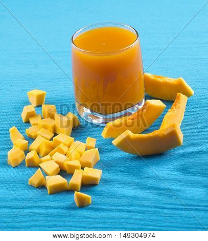 Pumpkin Juice. Pumpkin Juice In A Glass On A Blue Background, The Pumpkin Is Cut Pieces.