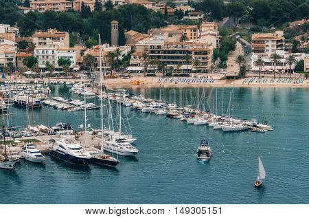 View over the bay of Puerto de Soller. Fishing boat returns to port de Soller after daily fishing Mallorca Balearic islands Spain