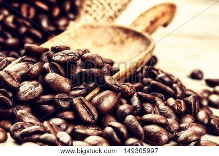 Roasted coffee beans with old wooden scoop. Close up